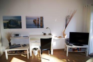 Studio mit TV und Schreibtisch