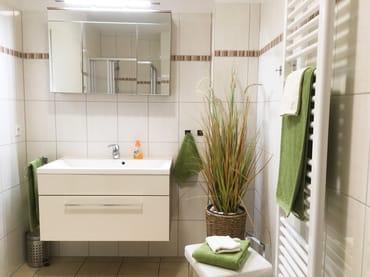 Das große und moderne Duschbad bietet genügend Platz für die ganze Familie. So verfügt das Bad über eine Wäschebox, einen Sitzhocker sowie einen Tritthocker für die kleinen Gäste.