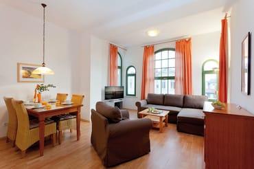 In dem großzügigen Wohnbereich wartet eine gemütliche Sitzecke mit bequemen Polstermöbeln zum Entspannen auf Sie. Von hier genießen Sie sogar einen Hauch Meerblick.