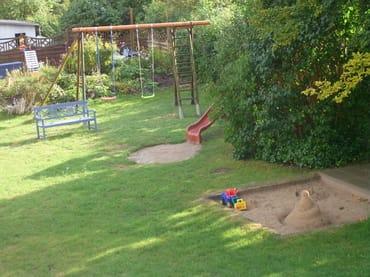 Der Spielplatz mit großem Sandkasten, Spielhaus mit Rutsche und Schaukel wird Ihre Kinder begeistern.