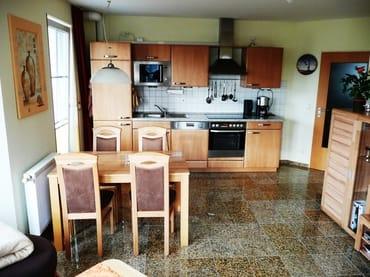 Wohnzimmer mit Essecke und integrierter Küche