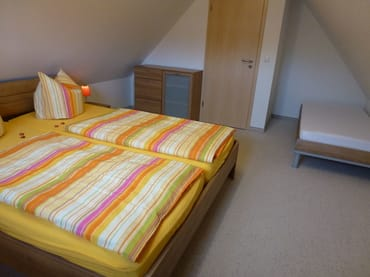 Schlafzimmer 2 mit Doppelbett und 1 Einzelbett und SAT-TV im Dachgeschoss