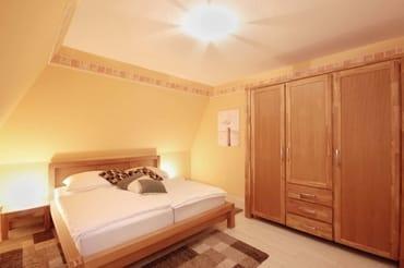 das Schlafzimmer mit Doppelbett und einem großem Kleiderschrank sowie Safe