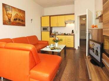 Wohnbereich mit gemütlicher Sitzecke mit integrierter Küchenzeile