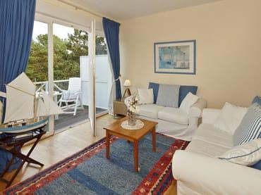 großzügiges Wohnzimmer mit Sitzecke und Zugang zum Balkon