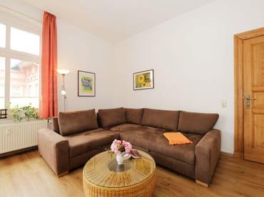 großes Wohnzimmer mit Sitzecke, Eßplatz und Zugang zu einem kl. Balkon