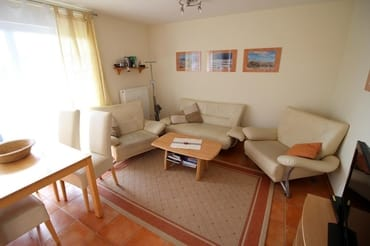 Wohnzimmer hat  bodentiefe Fenster und elektrische Aussenrollos.