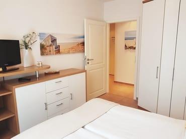Das Schlafzimmer mit Blick zum Flur. Der Kleiderschrank mit ausreichenden Kleiderbügeln bietet viel Platz für Ihre Urlaubskleidung.