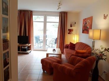 Das Wohnzimmer mit angenehmen Lichtquellen und dem angrenzenden Westbalkon. Links befindet sich die Küchenzeile mit dem Eßbereich.