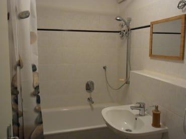 Bad mit Badewanne und Duschvorrichtung.
