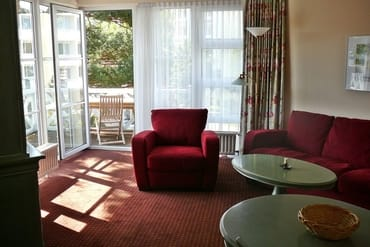 Hier die  Couchgarnitur, im Hintergrund der Balkon, von einer Kiefer teilweise angenehm beschattet. Panoramafenster und Balkon sind jeweils rechtwinklig angeordnet.