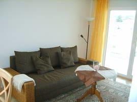 Wohnzimmer mit gemütlicher Couch, TV , Radio und direktem Zugang zum Westbalkon