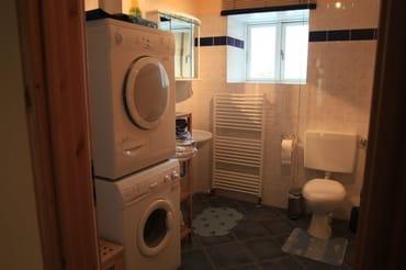 Badezimmer, linke Seite mit Waschbecken, Toilette, Waschmaschine und Wäschetrockner