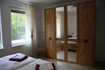 Elternschlafzimmer mit Doppelbett (1,80x2,00 m), großem Kleiderschrank und zwei Nachtkonsolen.