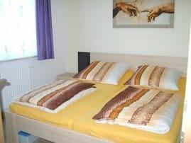 Schlafzimmer mit Doppelbett, großem Schrank und Fernseher