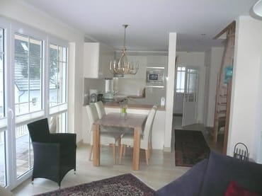 Essbereich mit dimmbarem Kronleuchter. 6 Stühle, im Hintergrund die offene Küche, rechts die Treppe in den Schlafbereich, links Zugang zum zusätzlichen Balkon,  Balkontür mit Fliegengitter
