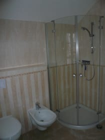 Bad im Schlafgeschoss mit Waschbecken, Ganzglasdusche, Toilette, Fußbodenheizung, Handtuchheizkörper und Außenfenster (nicht zu sehen) mit Fliegengitter