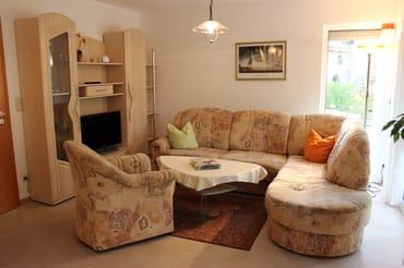 Der Wohnbereich mit bequemer Eckcouch mit zwei einzeln ausziehbaren Federkernbetten, Sessel, Leselampe und großem Fernseher