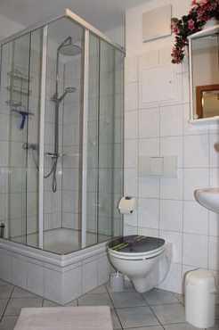 Badezimmer rundum gefließt mit beleuchtetem Spiegelschrank