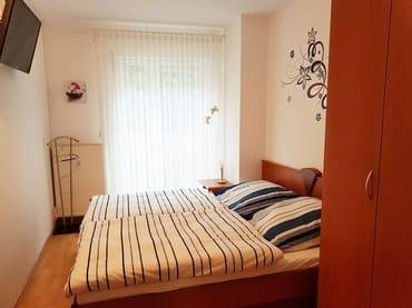Schlafzimmer mit Doppelbett, Süpiegelschrank und TV