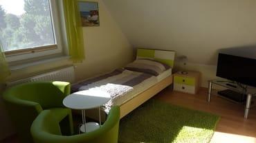 Schlafzimmer mit zwei Einzelbetten, TV und kleiner Stereoanlage im DG