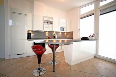 Voll ausgestattete Küchenzeile mit Tür zum kleinen Balkon
