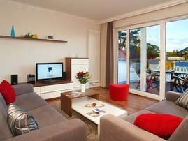 Im  exklusiven Wohnbereich können Sie auf den zwei gemütlichen Sofas die Seele baumeln lassen. Dank moderner Technik wie Flat-TV und DVD-Player entgehen Sie auch bei Regentagen der Langweile...