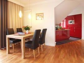 ...der angrenzende Esstisch kann ebenfalls für spannende Spieleabende genutzt werden. Die moderne Küche im edlen Rot bietet jeglichen Komfort und lässt aufgrund ihrer Ausstattung keine Wünsche offen.