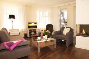 Der moderne Wohnbereich mit Relaxsessel, Sofa, Gaskamin, Flat TV,  iPad und Sonosanlage garantiert erholsame Urlaubstage zu jeder Jahreszeit.