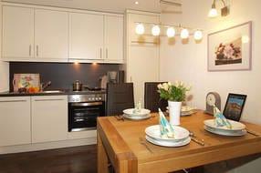 Die im Wohnbereich integrierte Küche mit Esstisch für 4 Personen bietet jeglichen Komfort und lässt aufgrund ihrer Ausstattung keine Wünsche offen.