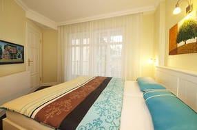 Das Appartement verfügt über ein Schlafzimmer mit Doppelbett und Flat TV sowie über einen weiteren Zugang zum Balkon.