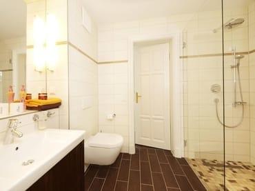 Im edlen Badezimmer, welches einerseits vom Schlafzimmer als auch vom Flur begehbar ist, wartet eine Dusche im XXL-Format auf Sie.