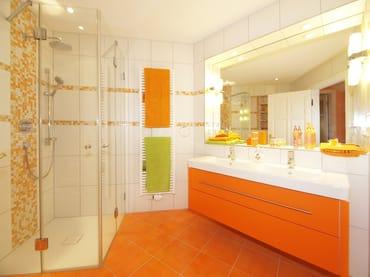 Im Badezimmer befindet sich eine ebenerdige, vollverglaste Regenwalddusche und ein Doppelwaschtisch - sowie ein WC und ein Haarfön.