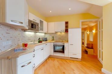 Die im Wohnbereich integrierte Einbauküche lässt jedes Kochherz höher schlagen.