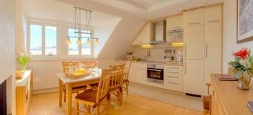 Die im Wohnzimmer integrierte hochwertige Küchenzeile ...