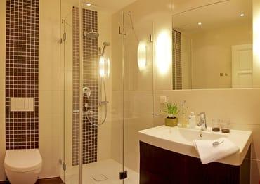 Das Badezimmer überzeugt mit einer Raindance-Dusche und einer superflachen Duschtasse im edlen Design.