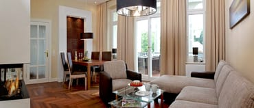 Die Einrichtung des Appartements ist in beigen und braunen Tönen gehalten, wodurch eine gelungene Mischung zwischen Moderne u. Historie entsteht.Die gemütliche Polstersitzecke lädt zum Entspannen..