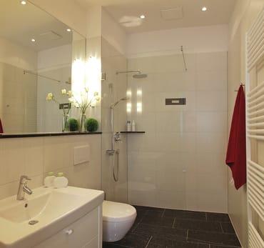 Das Appartement verfügt über ein edles Badezimmer mit bodengleicher Echtglasdusche und Kopfbrause sowie WC und einem Haarfön.