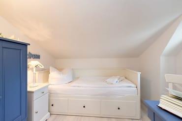 Das Bild zeigt das kleine Schlafzimmer mit einem Einzelbett in der Dachschräge.