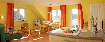 Wohnzimmer mit gemütlicher Couch sowie Essecke mit Blick zum Achterwasser