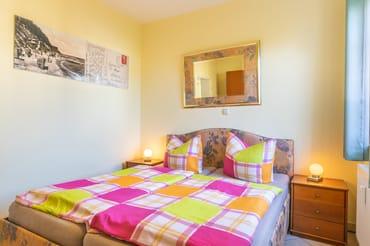 Schlafzimmer mit Doppelbett (Liegefläche 160 x 200 cm), Nachtschränkchen und einem geräumigen Schlafzimmerschrank.