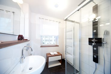 Das Bad mit Dusche, WC und Sichtschutzplissee am Fenster.