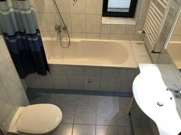 Badezimmer mit Badewanne und Handtuchtrockner