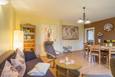 Das helle Wohnzimmer mit Blickrichtung Küche bietet Ihnen einen gemütlichen Aufenthalt.