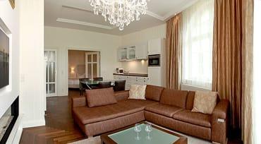 Das exklusive 3-Zimmer-Appartement verfügt über ein imposantes Wohnzimmer mit XXL-Ecksofa, Flat-TV, Gas-Kamin, schillerndem Kronleuchter und modernster Küchenzeile.
