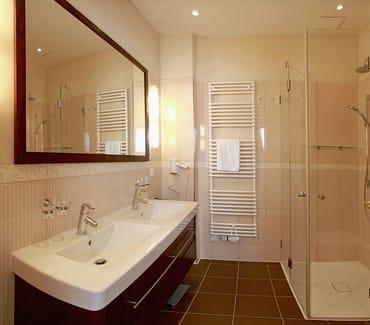 Das Badezimmer überzeugt mit einem Doppelwaschtisch, großflächigem Spiegel und einer bodengleichen Echtglasdusche.