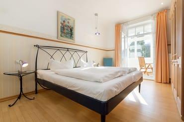 Vom Schlafzimmer mit Doppelbett und Kleiderschrank gelangen Sie in die Loggia.
