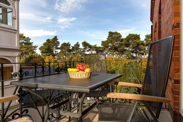 Die Ferienwohnung DolceVita hat einen schönen Balkon mit typischem schmiedeeisernen Geländer und wunderbarem Blick auf die Seebrücke und die Ostsee. Der Meerblick variiert mit Schnitt der Dünenbäume.
