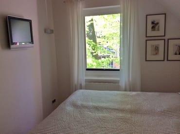 Schlafzimmer mit Naturholzbett und einer Ferderkernmatratze , TV zum abendlichen Abtauchen, direkter Zugang zum Badezimmer, Insektenschutz vor dem Fenster