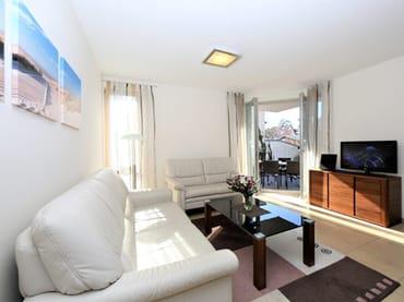 gemütlicher Wohnbereich mit Zugang zur sonnigen Terrasse